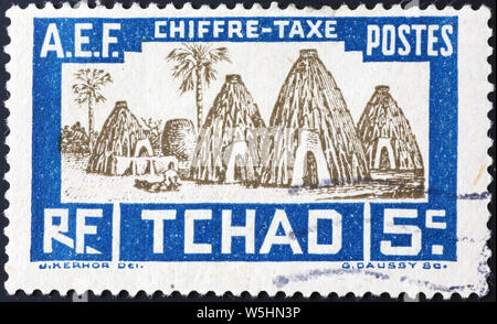 Huts on old postage stamp of Chad - Stock Photo