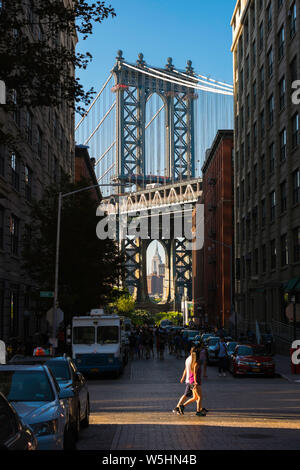Brooklyn summer, view along Washington Street of Dumbo and the Manhattan Bridge with young people in the foreground, Brooklyn, New York City, USA - Stock Photo