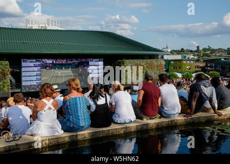 Fans and spectators on Henman Hill , Murray Mound or Aorangi Hill with the big screen on No.1 Court during The Championships at Wimbledon 2019. - Stock Photo