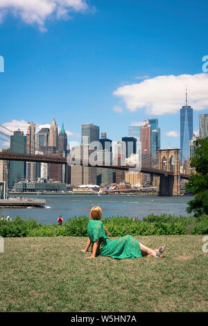 New York skyline, rear view of a woman relaxing in Main Street Park, Brooklyn, looking at the Lower Manhattan skyline, New York City.