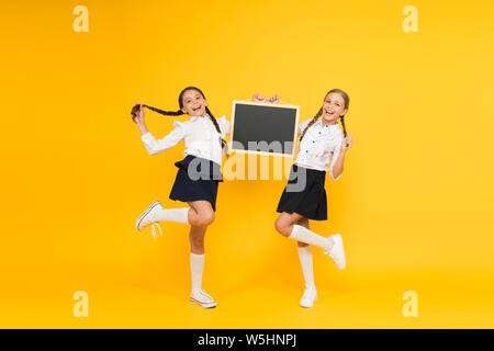 Back to school. Happy children holding school blackboard on yellow background. Little girls preparing for school lesson. Small kids smiling in school uniform on september 1, copy space. - Stock Photo
