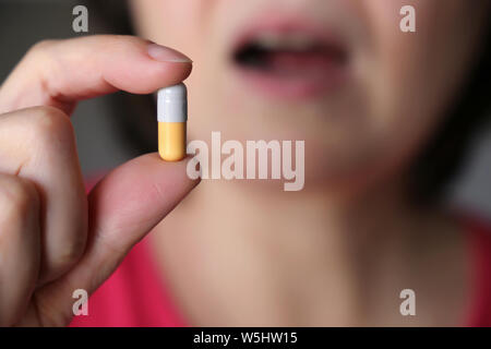 Woman takes a pill, girl putting capsule in mouth. Sick female taking medicines, painkiller, antibiotic or vitamin - Stock Photo