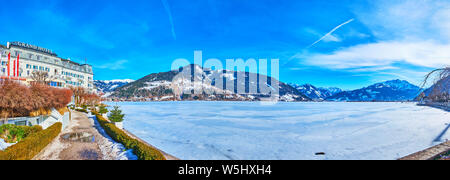 ZELL AM SEE, AUSTRIA - FEBRUARY 28, 2019: Panorama from embankment of Elisabeth park with a view on Zeller see, covered with ice, Alps and Grand Hotel - Stock Photo