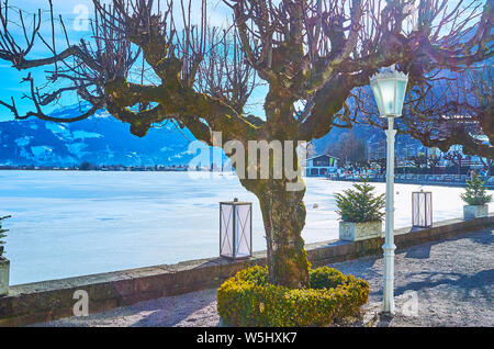 The view on Zeller see lake through the old tree, vintage lanterns and trimmed bush, Zell am See, Austria - Stock Photo