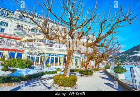 ZELL AM SEE, AUSTRIA - FEBRUARY 28, 2019: The classic building of Grand Hotel is decorated with small topiary garden, facing Zeller See lake, on Febru - Stock Photo