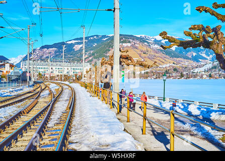 ZELL AM SEE, AUSTRIA - FEBRUARY 28, 2019: The cityscape with railroad, winter Elisabeth park, frozen Zeller See lake and luxury Grand Hotel on backgro - Stock Photo