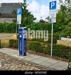 Gifhorn, Germany, July 7., 2019: Charging station for electric cars on the parking lot of a small town, with hedges and a lawn in the background - Stock Photo