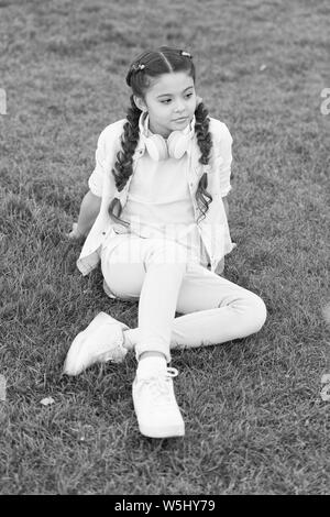 Get happy yourself. Girl braids hairstyle and modern headphones enjoy relax. Secrets to raising happy child. Girl cute kid green grass background. Healthy emotional happy kid relaxing outdoors. - Stock Photo
