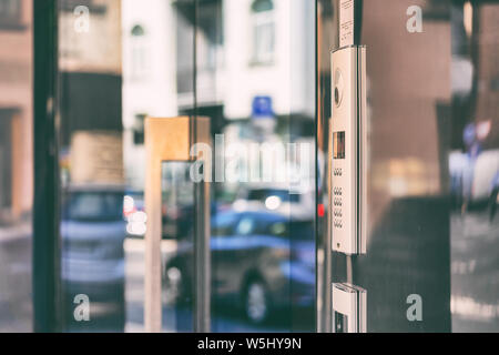 Code lock with buttons and a map on glass doors with a reflection of cars on the street on a summer day - Stock Photo