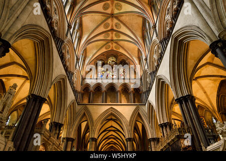 Vaulted ceiling with pillars and arches and stained glass window of Moses above the sanctuary of medieval Salisbury Cathedral Salisbury England - Stock Photo