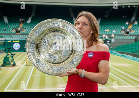 Simona Halep (ROU) with the 2019 Wimbledon Ladies' Singles Trophy on Centre Court at The All England Lawn Tennis Club, Wimbledon. - Stock Photo