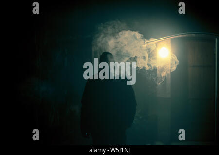 strange man smoking at night with big steam effect from the cigarette - Stock Photo