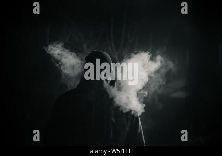 man silhouette smoking like chimney at night with backlight - Stock Photo