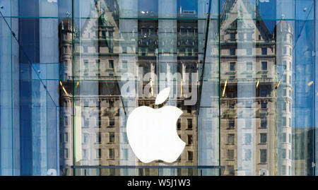 New York, USA, November 2016: Detail of the Apple logo with the Plaza hotel facade reflected on the glass wall at the Apple Store on New York's fifth - Stock Photo