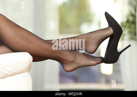 Side view portrait of a woman legs with stockings taking off shoes on a couch at home - Stock Photo