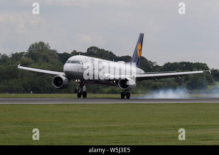 A Lufthansa Airbus A320-200 lands at Manchester International Airport (Editorial use only) - Stock Photo
