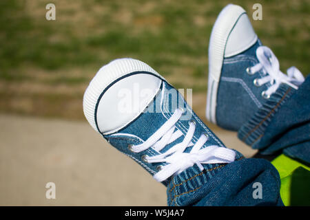 Feet of a baby sneakers, selective focus - Stock Photo