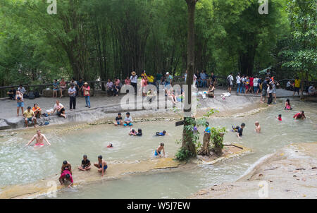 People enjoying the water by the Sai Yok Noi Waterfall in the Tenasserim Hills, Sai Yok District of Kanchanaburi Province, Thailand - Stock Photo