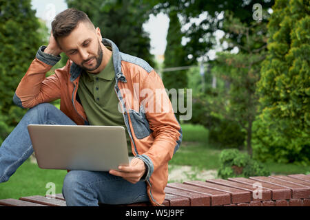 Young, successful freelancer working on laptop, sitting on wooden bench in spring green garden. Handsome, concentrated man in stylish clothing looking at laptop. - Stock Photo