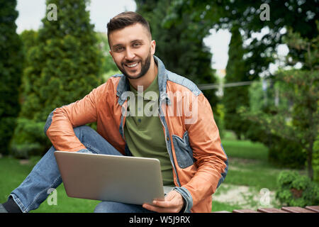 Handsome, stylish, young man sitting on wooden bench in green garden, looking at camera, smiling. Student using laptop for study and work. Concept of lifestyle. - Stock Photo