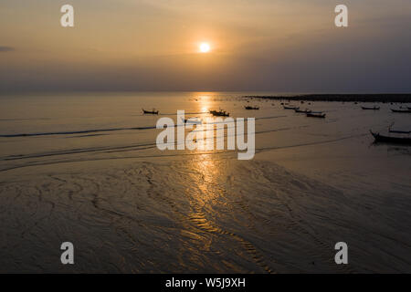Aerial drone view of traditional longtail boats at anchor during a tropical sunset over the ocean - Stock Photo