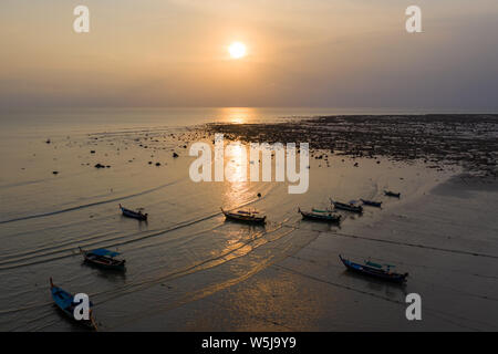 Aerial drone view of sunset over a shallow, tropical ocean with traditional wooden longtail boats at anchor - Stock Photo