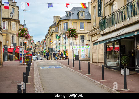 Tourists and local French walk the long, one way Rue Saint-Jean main street past cafes and shops in the Normandy town of Bayeux, France - Stock Photo
