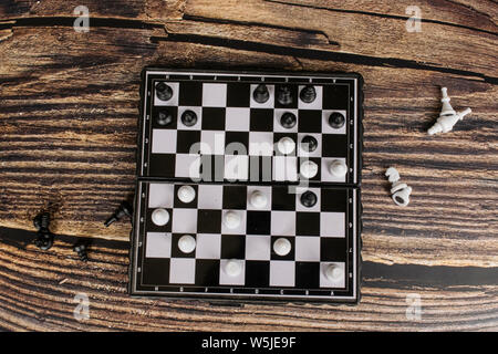 Small pocket chess on a wooden table. - Stock Photo