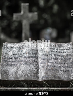 Headstone and fading pages from bible in West Brompton Cemetery in West London, England, UK. - Stock Photo
