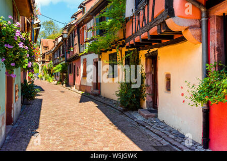 colorful picturesque lane in the old town of Kaysersberg, Alsace Wine Route, France, half-timbered houses with flower decoration - Stock Photo