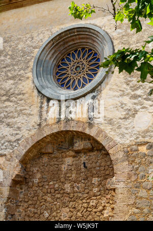 Detail shot of the royal charter house of Jesus of nazareth in Valldemossa - rough brick wall with a beautiful round window behind green leaves - Stock Photo