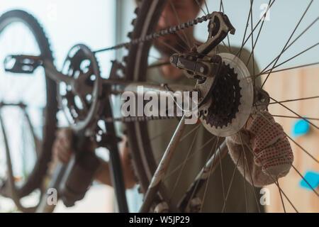 Man repairing old hardtail mountain bike in workshop, selective focus
