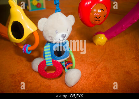 Baby accessor teether, caterpillar toy, teddy bear, background top view - Stock Photo