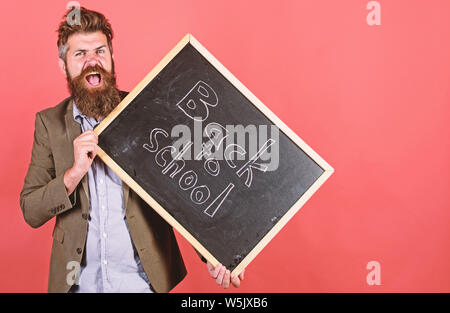 Teaching stressful occupation. Teacher with tousled hair stressful about school year beginning. Stay positive. Teacher bearded man holds blackboard with inscription back to school red background. - Stock Photo