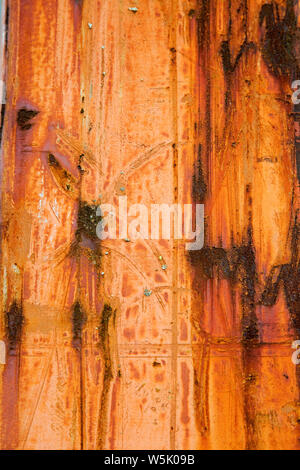 Rusted orange painted steel sheet shot portrait for use as a texture background or cover - Stock Photo
