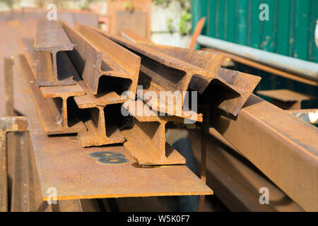 A heap of rusted iron girders or rolled steel joists left outside in a yard - Stock Photo
