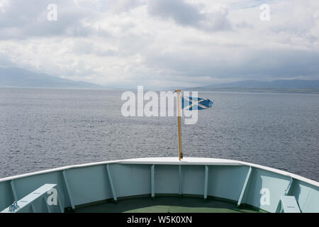 Scottish flag on the bow of a Caledonian Macbrayne ferry leaving the port in Oban, Scotland, travelling towards the Isle of Islay. - Stock Photo