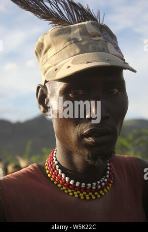 A Young Turkana Man wearing a modern cap with an Ostrich feather inserted on Top - Stock Photo