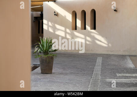 DOHA, QATAR - MAY 27, 2016:  Empty courtyard at the Katara Cultural Village with structure casting shade patterns. Photo taken at the end of a spring - Stock Photo