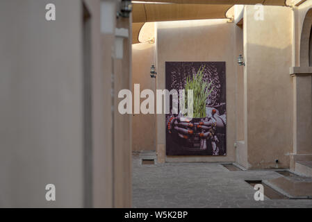DOHA, QATAR - MAY 27, 2016:  Poster of a flower pot at the Katara Cultural Village. Photo taken at the end of a spring afternoon. - Stock Photo