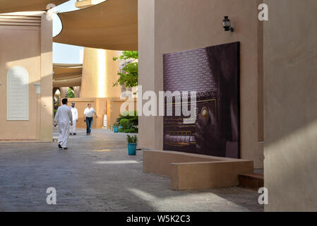 DOHA, QATAR - MAY 27, 2016:  Passersby and poster of a vintage radio at the Katara Cultural Village. Photo taken at the end of a spring afternoon. - Stock Photo