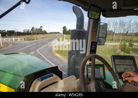 Sheffield, Canterbury, New Zealand, July 27 2019: A farmer drives a large modern John Deere tractor to a farm field on country roads - Stock Photo