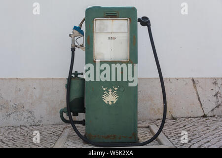Old antique green rectangular fuel pump standing by a wall in the main courtyard area of the Art District of the Citadel of Cascais, Cascais, Portugal - Stock Photo