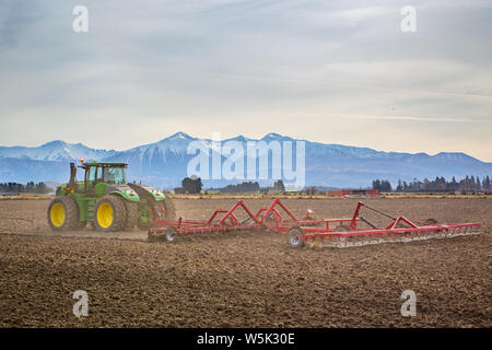 Sheffield, Canterbury, New Zealand, July 27 2019: A large modern John Deere tractor tows a cultivator in a field in winter - Stock Photo