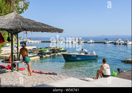 Tourists enjoy the beach at Brela. The Makarska riviera in Croatia is famous for its beautiful pebbly beaches and crystal clear water. - Stock Photo