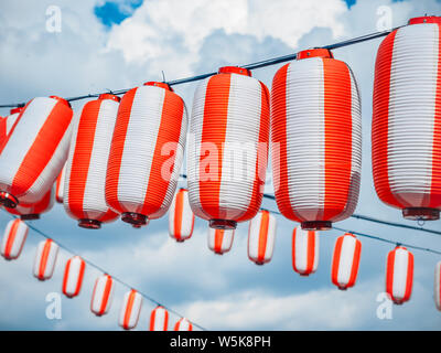 Paper red-white japanese lanterns Chochin hanging on cloudy blue sky background. Summer background - Stock Photo