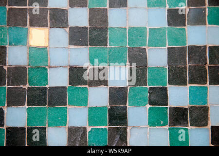 Little square ceramic mosaic tiles in blue and green and black and gold shades shot close up in landscape as a texture background - Stock Photo