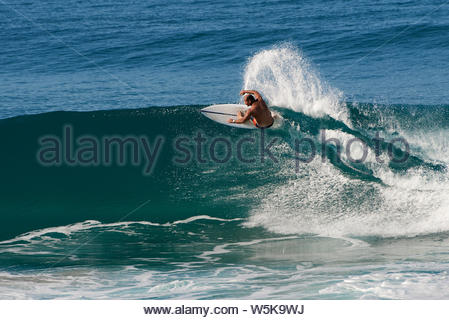 A male surfer performing a carving frontside top-turn off-the-lip, on a glassy-wave, during ideal surf conditions at Iluka; on Australia's east coast. - Stock Photo