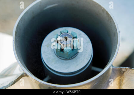 A close up shot of a castellated nut and split pin holding on a propellor on a boat - Stock Photo