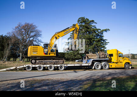Sheffield, Canterbury, New Zealand, July 10 2019: A digger is transported by a large truck to a work site in a rural area - Stock Photo